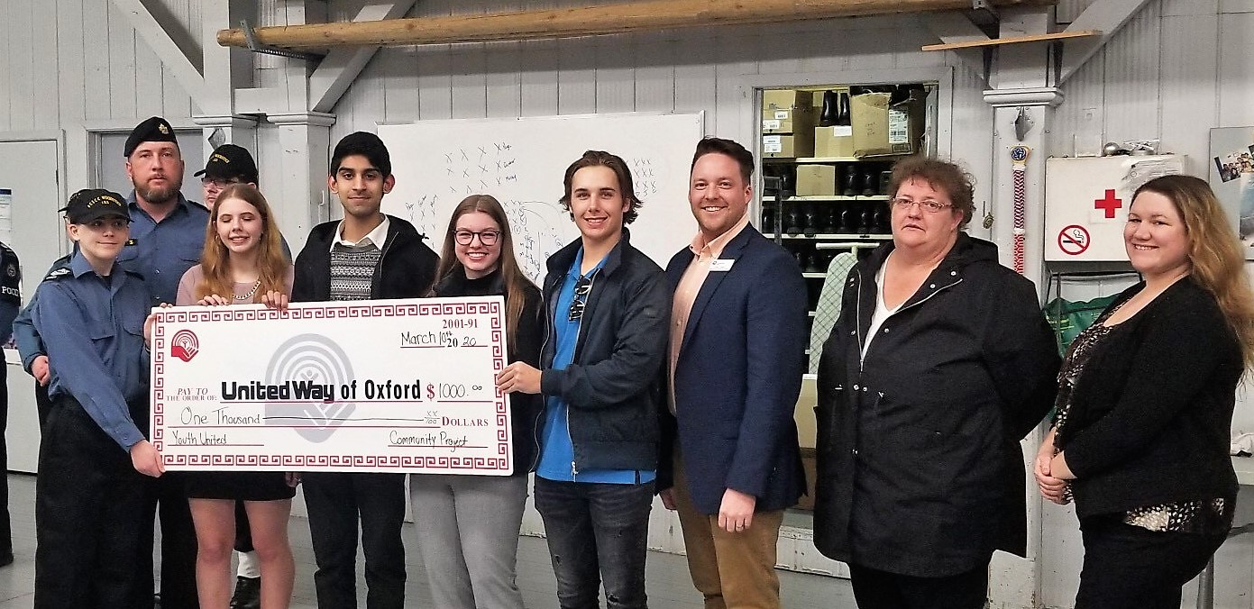 The Royal Canadian Sea Cadets Canada Woodstock pose with Youth United and Canadian Mental Health Association Oxford representatives with a large cheque for $1,000